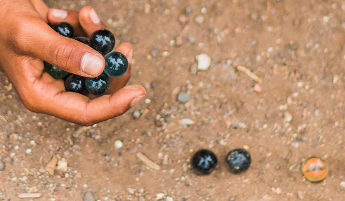 Hand holding marbles and rolling them along the ground.