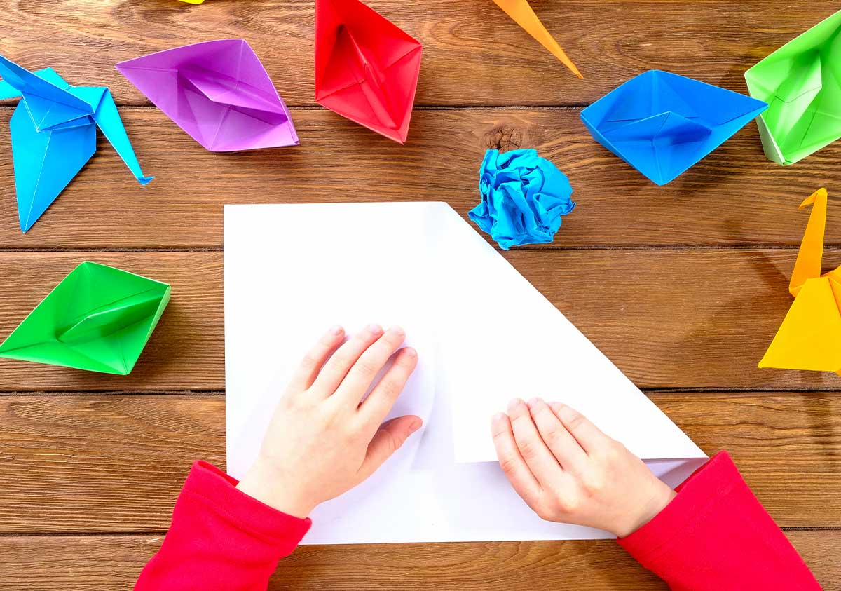 A child's hands folding paper to make origami Pokemon characters.
