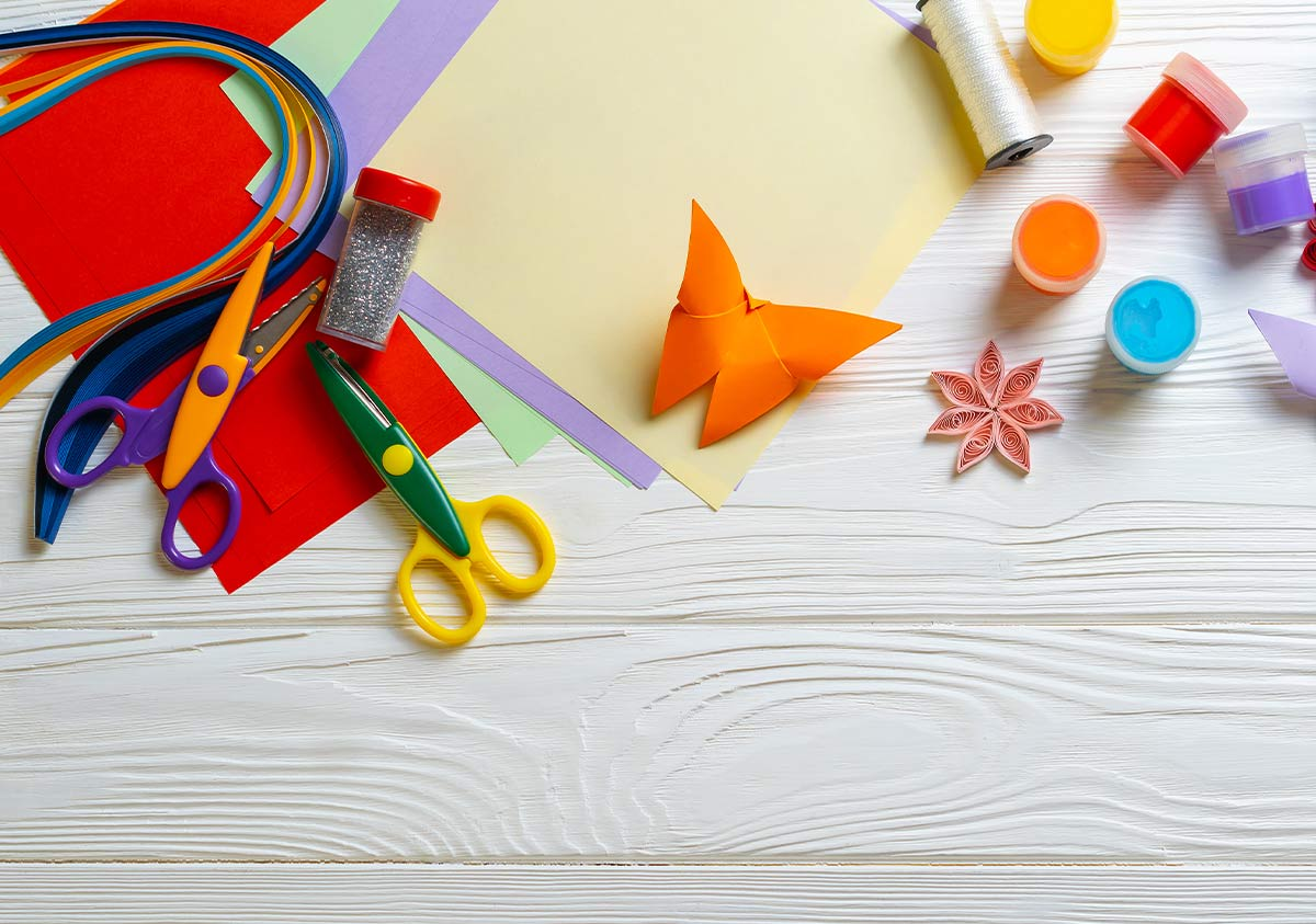 Art supplies to make origami on a table.