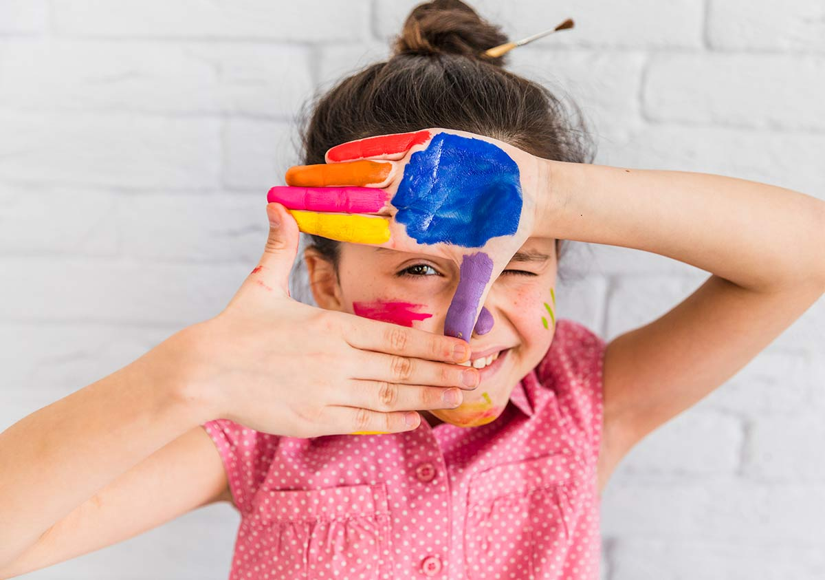 Young girl with paint on her hands making a sign framing her eye.