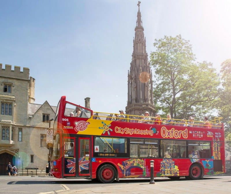A red open-top double-decker sightseeing bus stationery at a monument in Oxford.