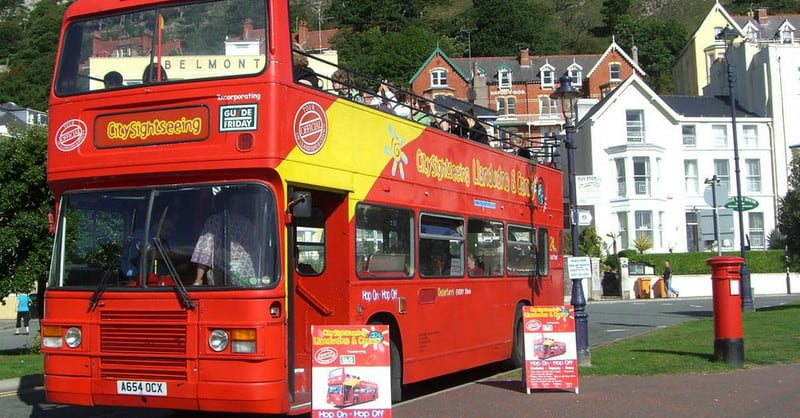 A red open-top double-decker sightseeing bus with two placard boards standing at the front of it.