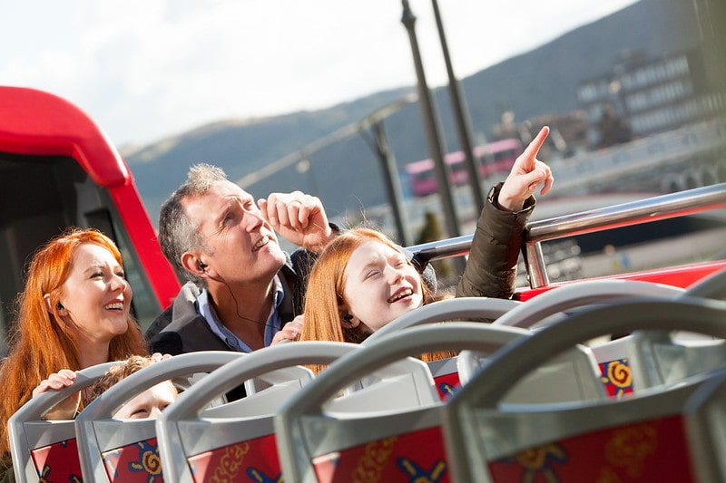 A family on an open-top sightseeing bus pointing at attractions.