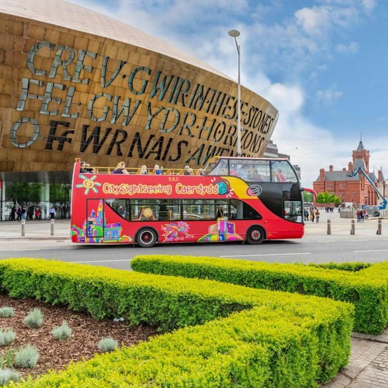 An open-top double-decker sightseeing bus driving past the Wales Millennium Centre in Cardiff.
