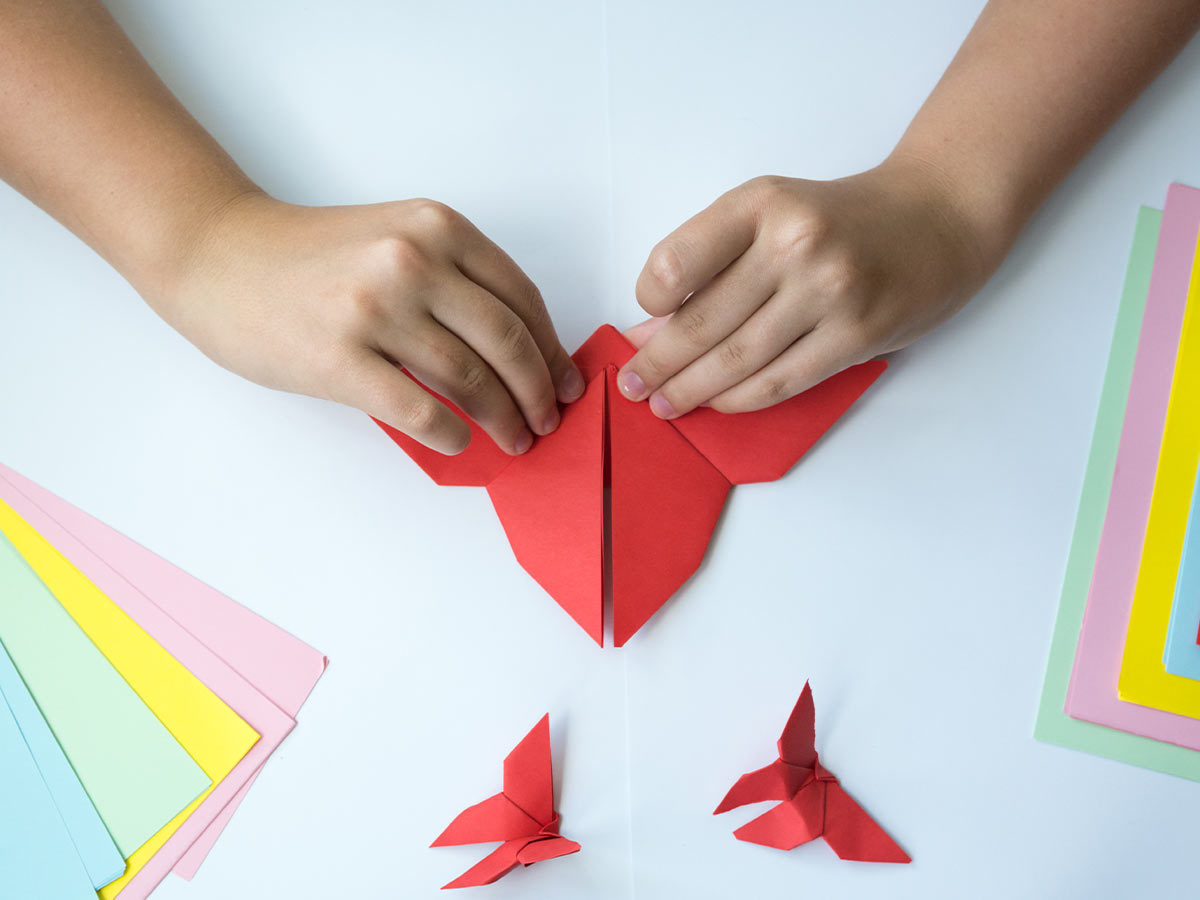 Close up of a child's hands folding red paper to make an origami hummingbird.