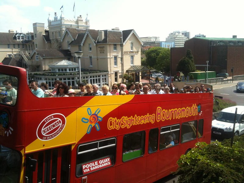 An open-top double-decker sightseeing bus with visitors sitting on the top deck.