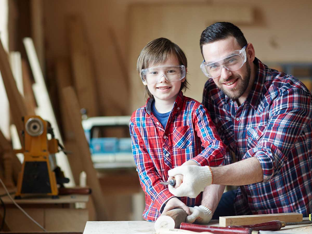 Father and son making a bird box together: they are smiling with the materials they need.