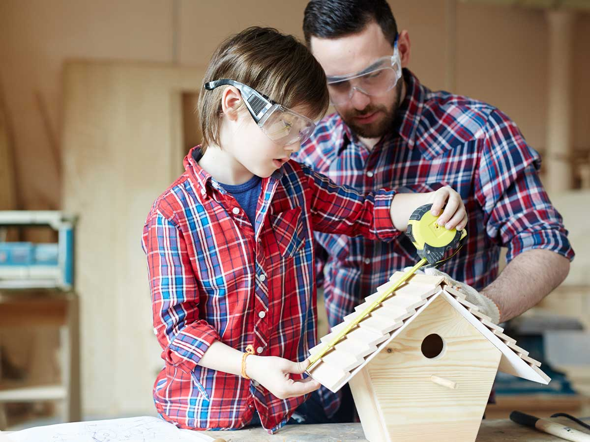 Father and son checking that their bird box is correct with a measuring tape.