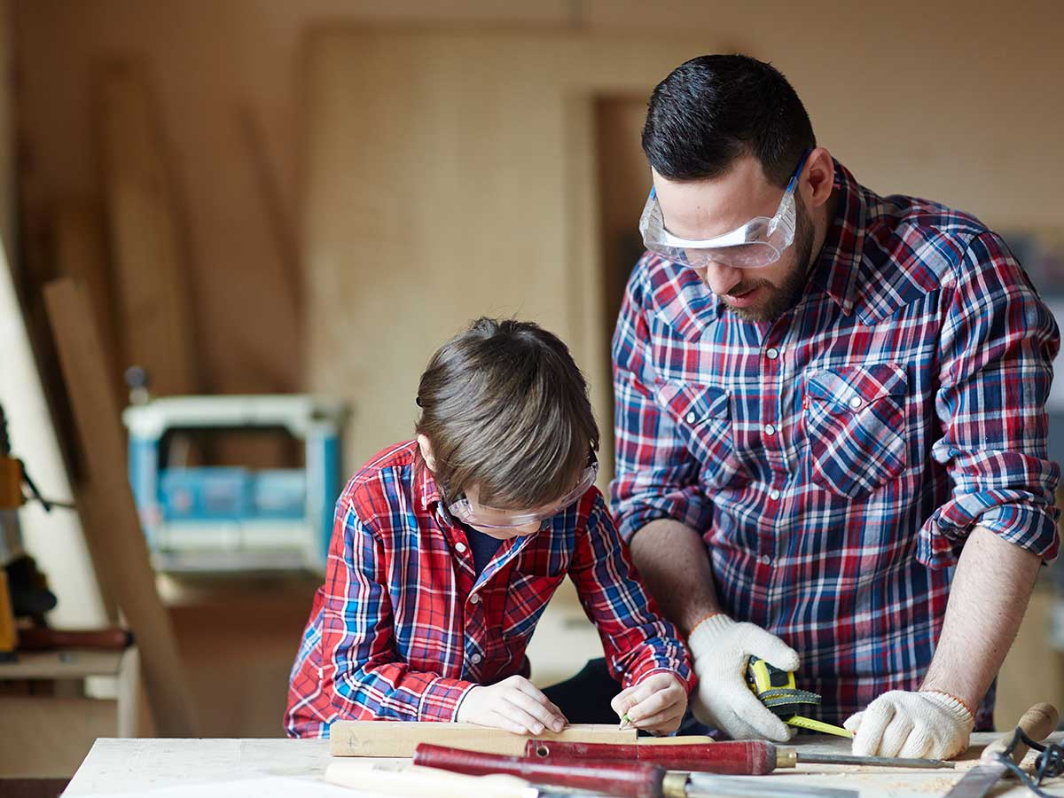 Father and son measuring the pieces of wood they need to make a bird box.