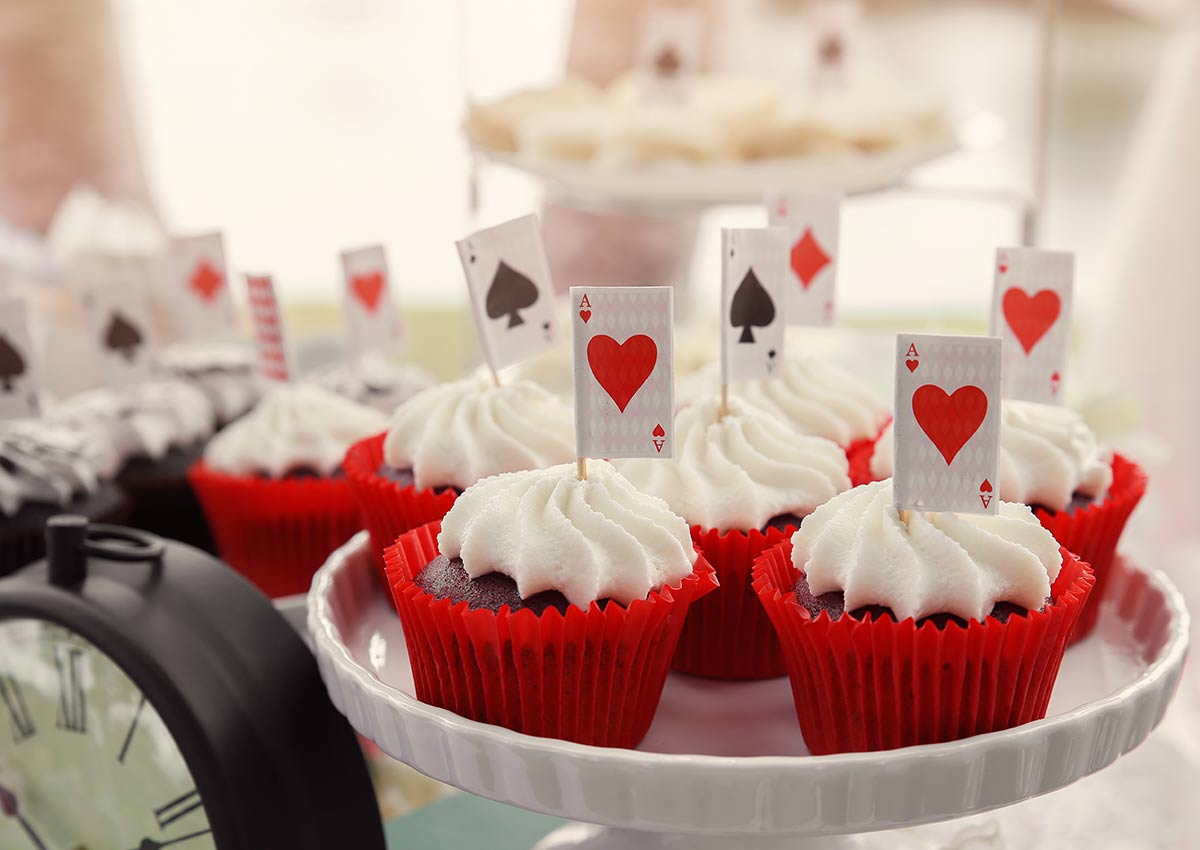 Cupcakes in red cases with decorations inspired by playing cards.