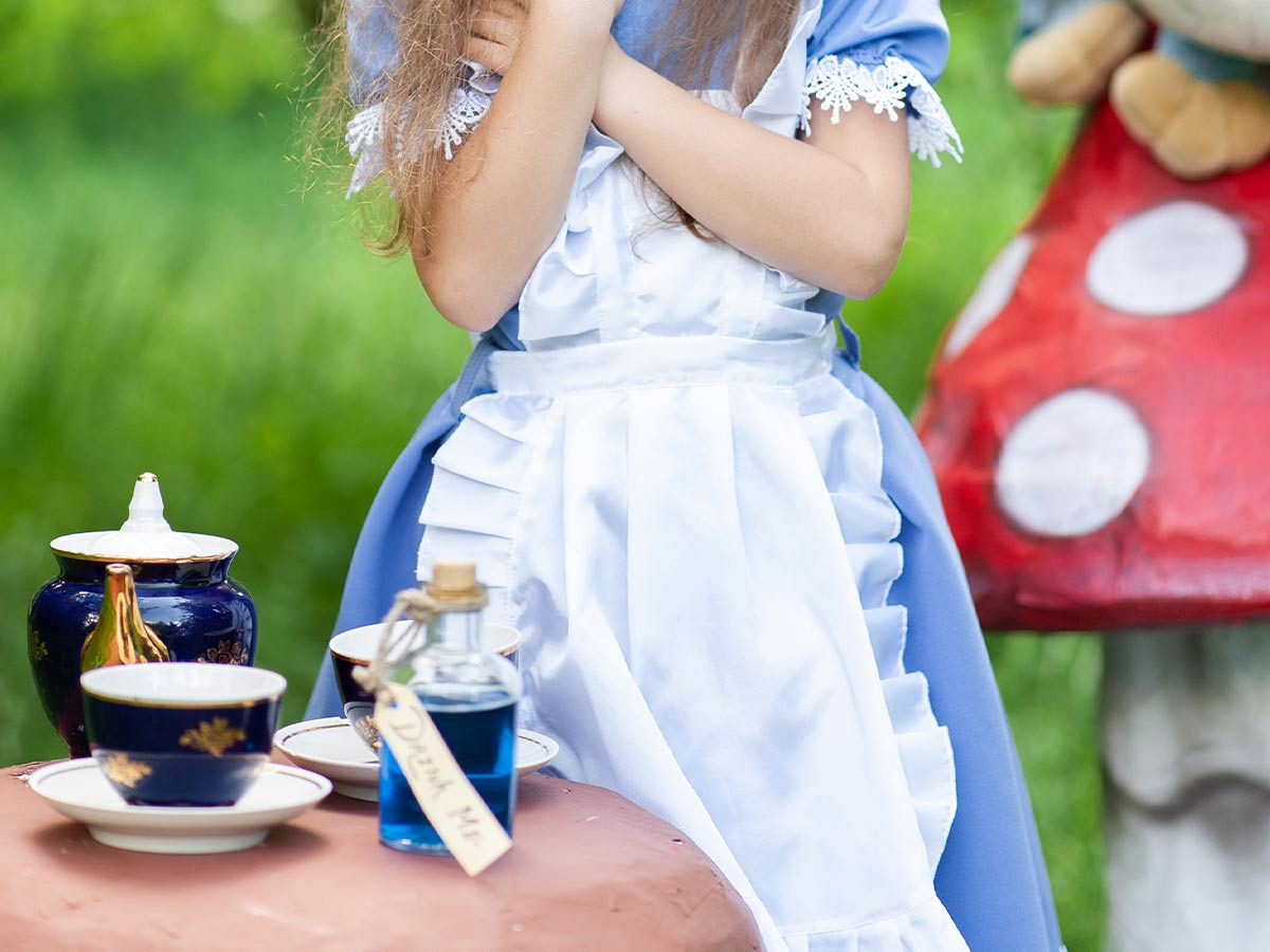 Girl dressed as Alice in Wonderland acting out the Madhatter's tea party.