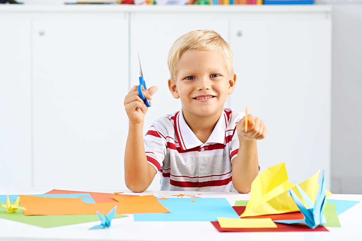 Boy smiling as he holds scissors and paper ready to make an origami bear.