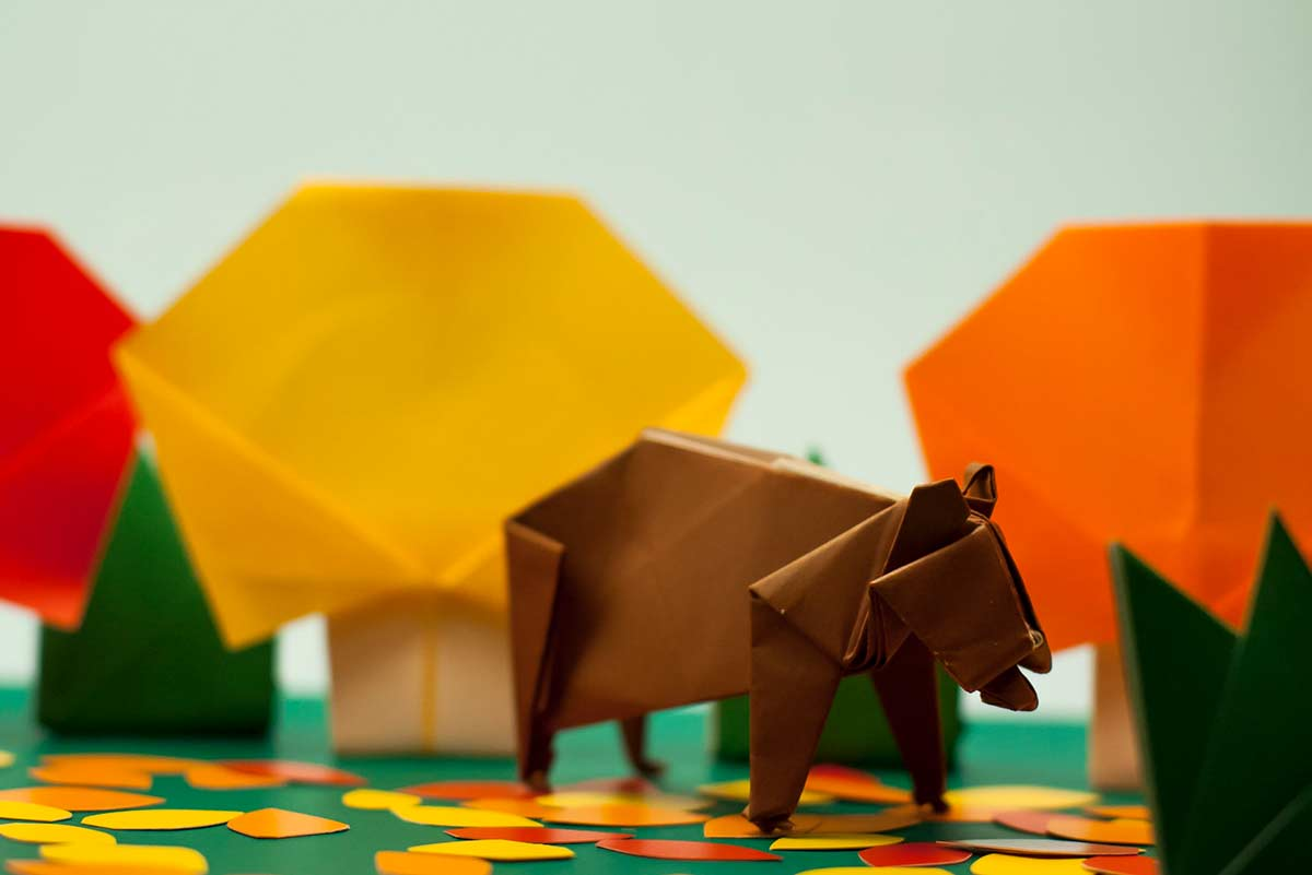 A brown origami bear on all fours with origami trees and in the background.