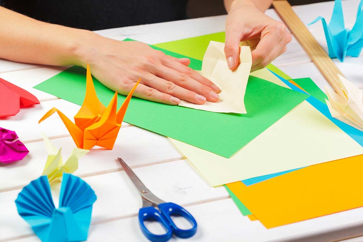 Close up of hands folding paper making an origami bear, with other origami animals dotted around the table.