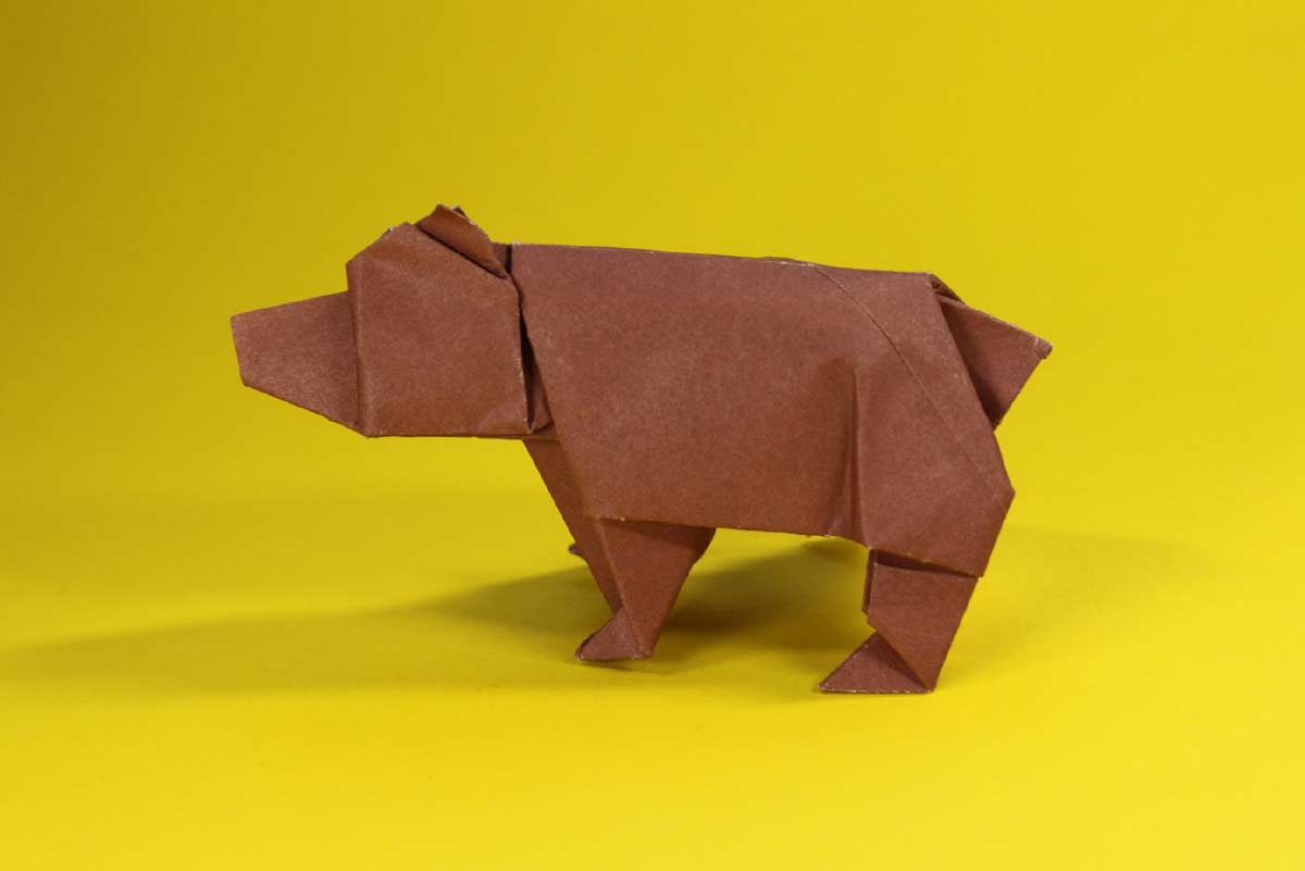 A brown origami bear against a yellow background.