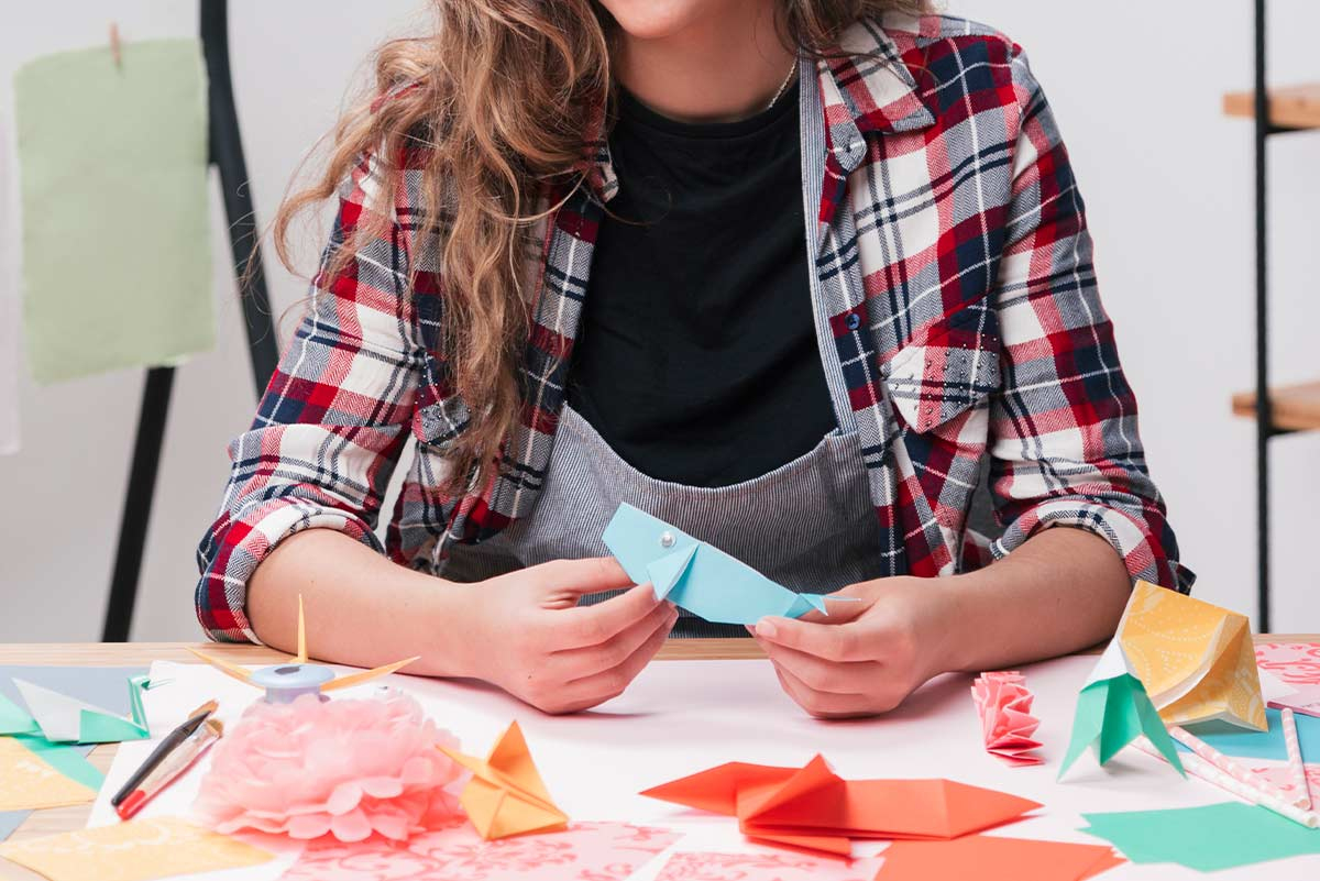 Close up of a woman folding an origami bear.
