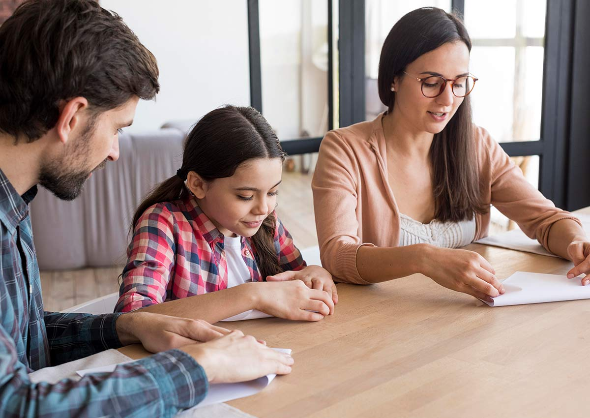 Girl and her parents sat at the table together folding a piece of paper each to make an origami robin.