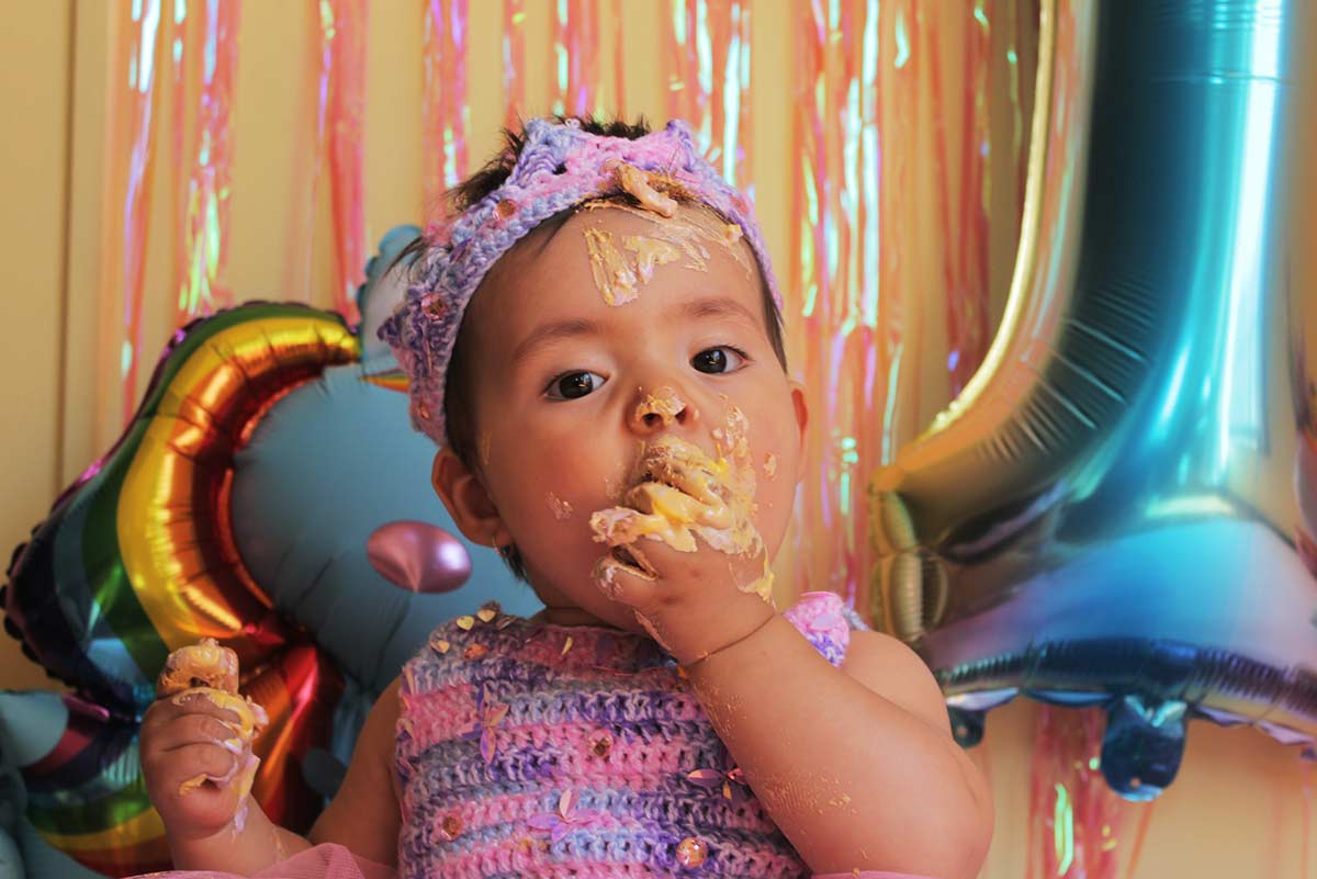 Toddler eating cake with her hands, icing all over her face and fingers.