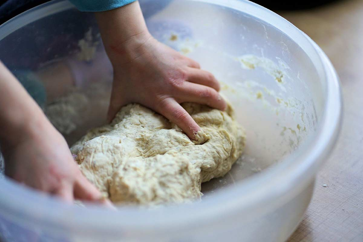 Close up of a child kneading dough.