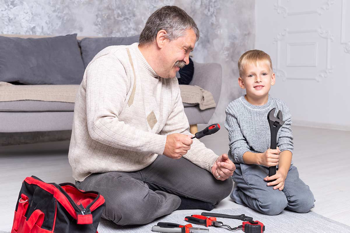 Grandpa and grandson sat on the floor with screwdrivers to make a toy robot.