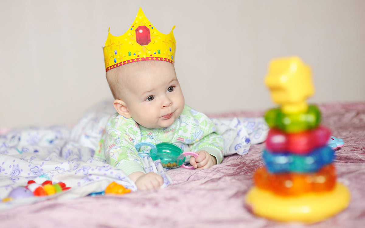 Baby boy wearing a prince's crown lying on his tummy in front of some toys.