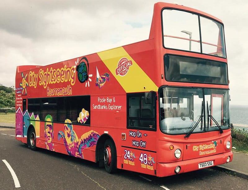 An open-top City Sightseeing tour bus parked by the beach in Bournemouth.