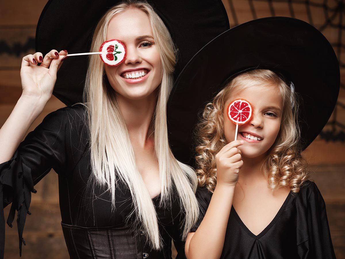 Two sisters dressed as witches holding lollipops in front of their eyes.
