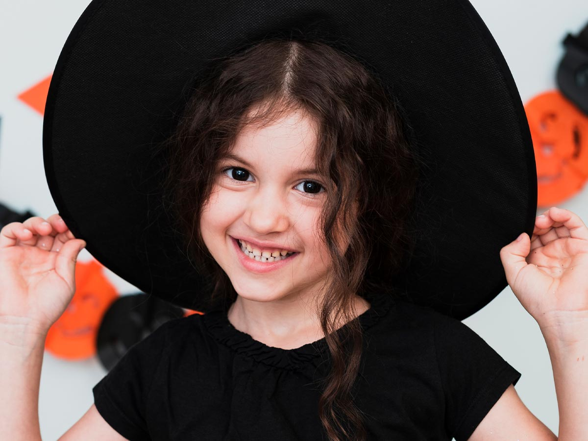 Little girl wearing a large black witch's hat smiling.