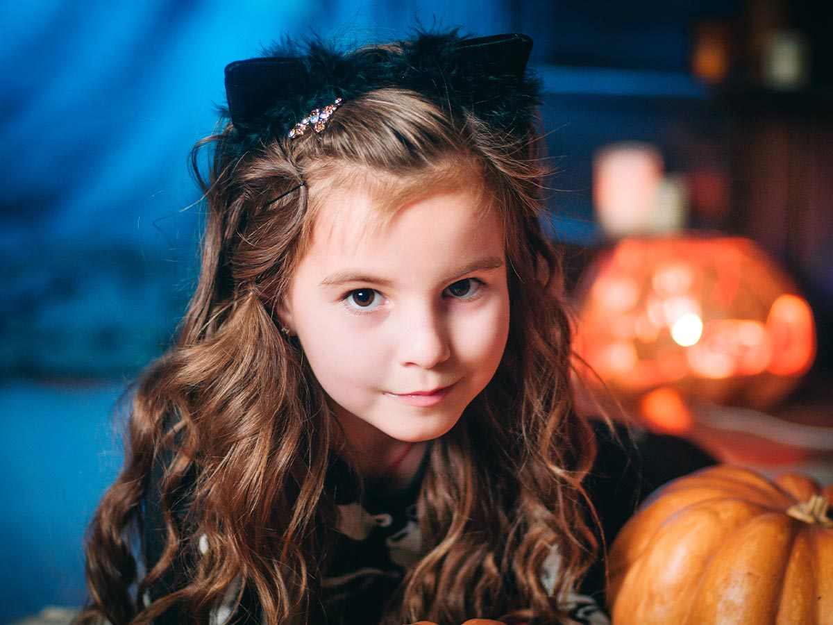 Young girl wearing black cat ears.