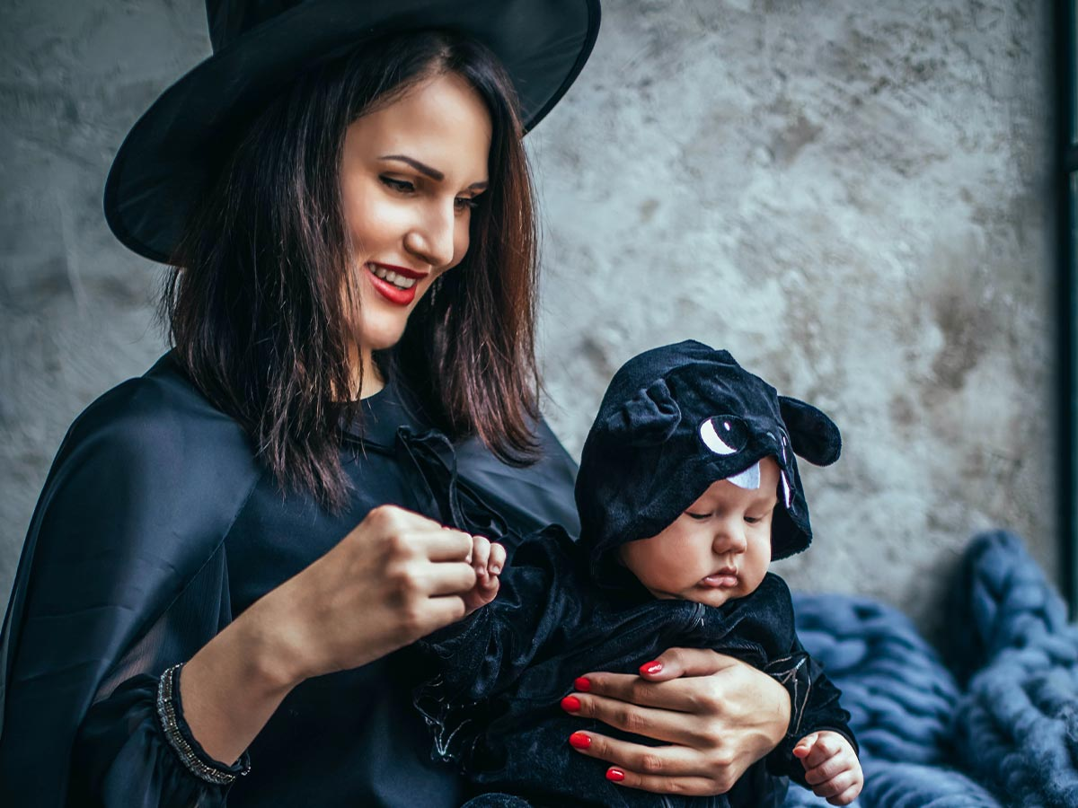 Mum dressed as a witch holding her baby girl dressed as a bat.