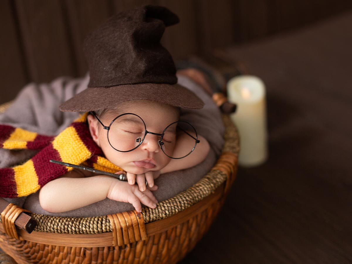 Baby boy wearing a Gryffindor scarf, sorting hat, Harry Potter glasses and holding a wand while he sleeps.