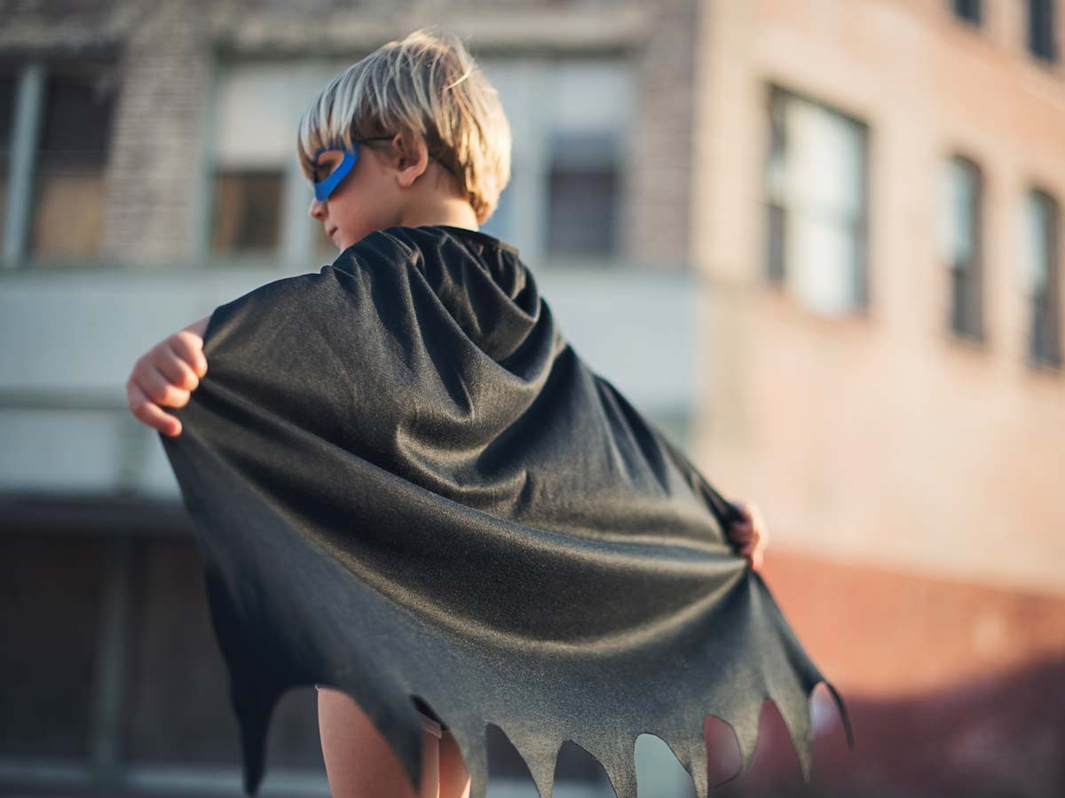 Young boy wearing a blue mask and a black cape.