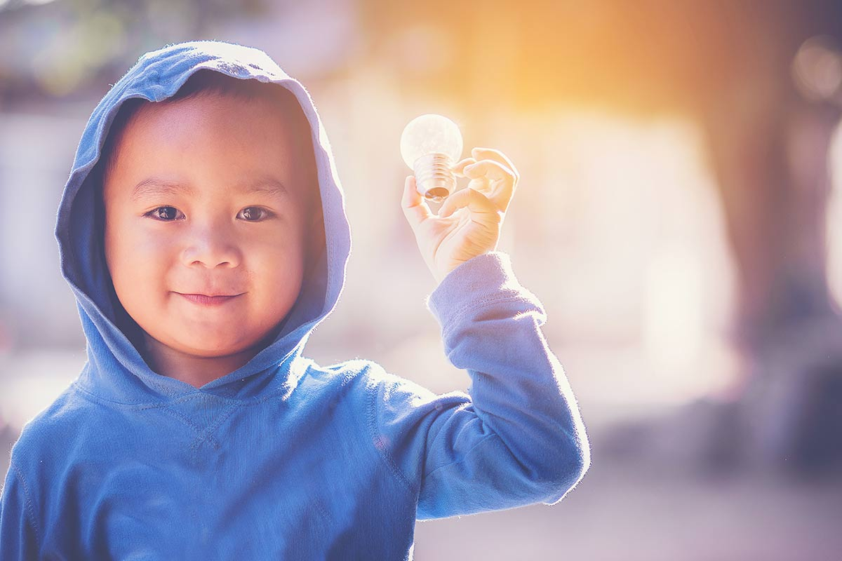 Young boy wearing a blue hooded jumper holding up a lightbulb.