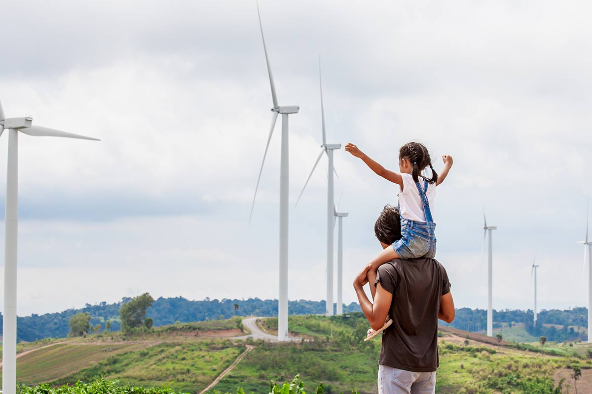 Little girl on her dad's shoulders standing on a hill looking at the wind turbines.