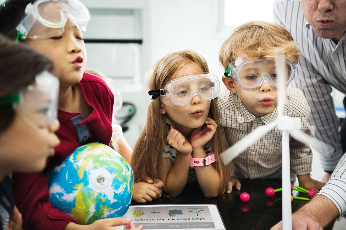Young children in science class wearing goggles looking at a model of a wind turbine.