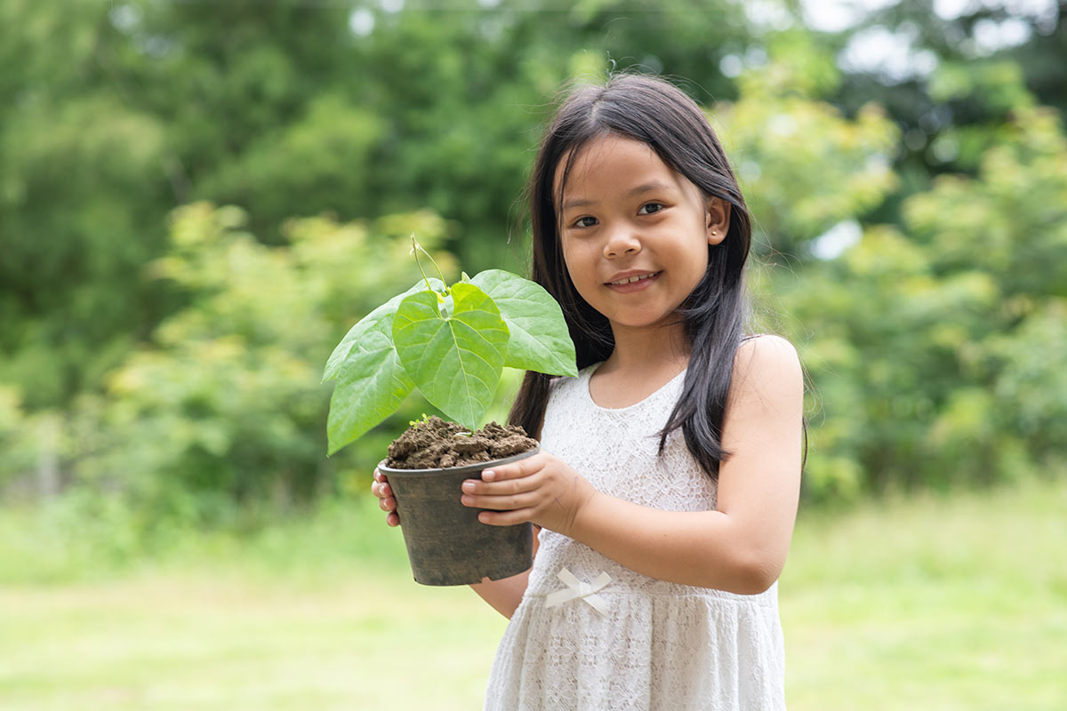 Young girl standing in a garden holding a plant in her hands smiling.