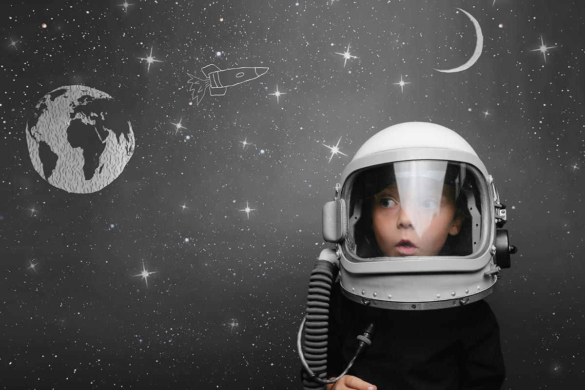 Young boy wearing an astronaut helmet standing in front of a blackboard with space drawings on it.n