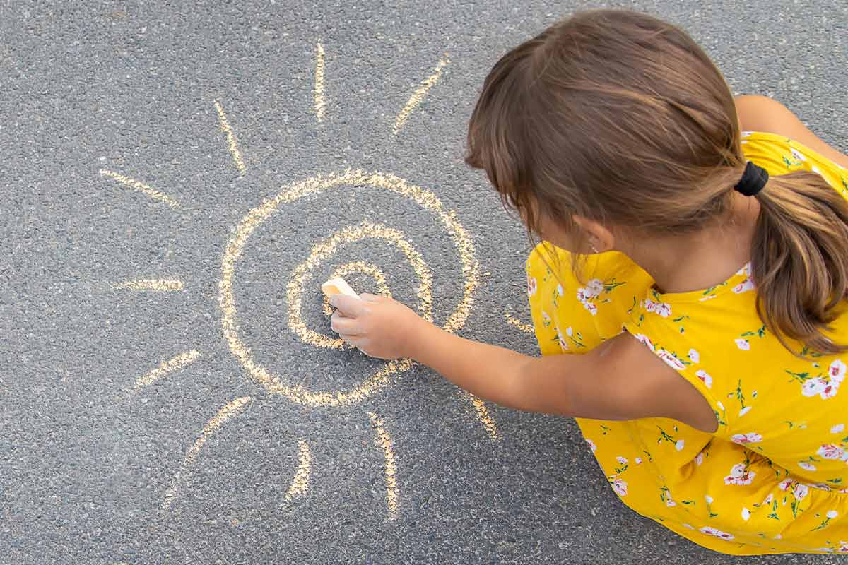 Little girl, wearing a yellow dress, crouching down drawing a sun, in yellow chalk, on the ground.