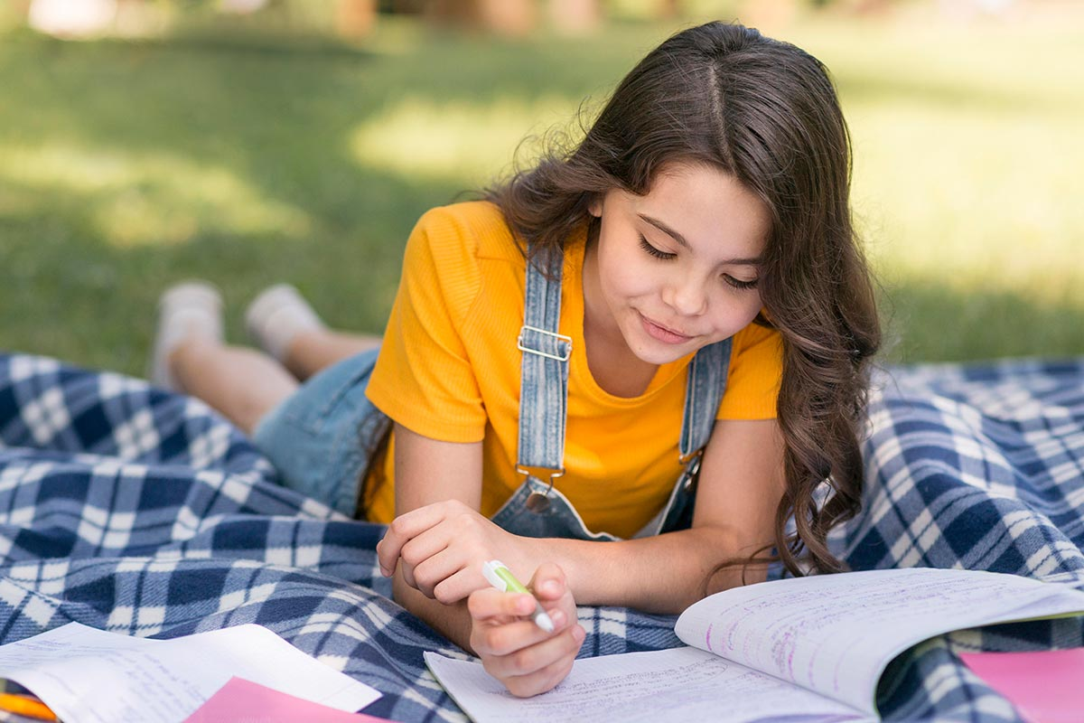 Young girl lying on her stomach on a rug outside, learning about hyphens writing in her workbook.