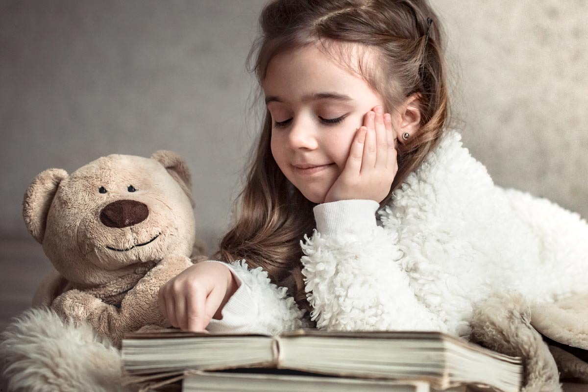 Young girl reading a book next to her brown teddy bear.