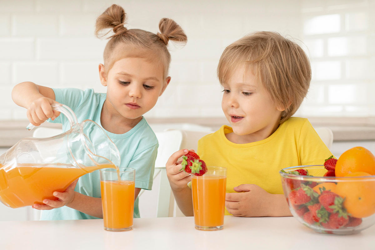 Young girl and boy in the kitchen, the girl is pouring a glass of orange juice for herself and her brother.