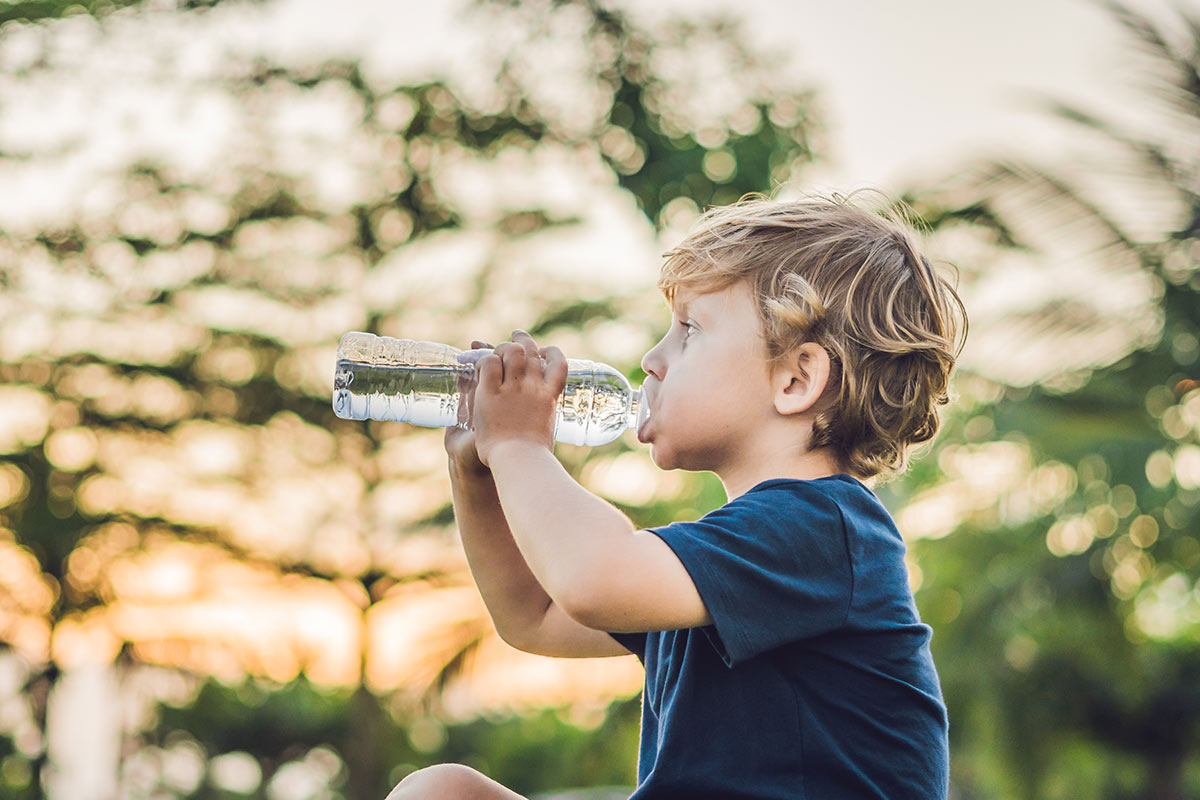 Young boy sat drinking water from a bottle in the garden.