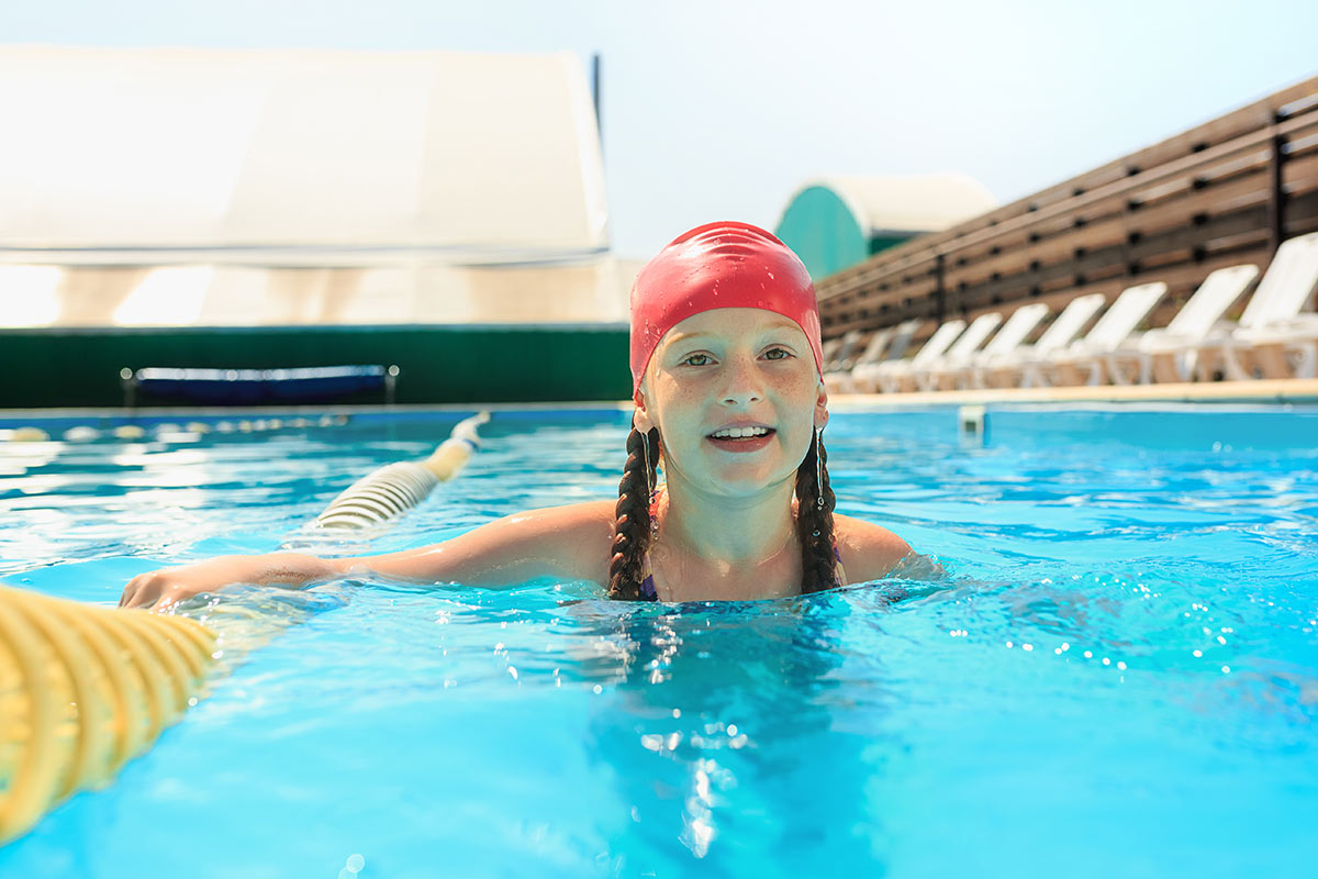 Young girl, wearing a red swimming cap, swimming in an outdoor pool.
