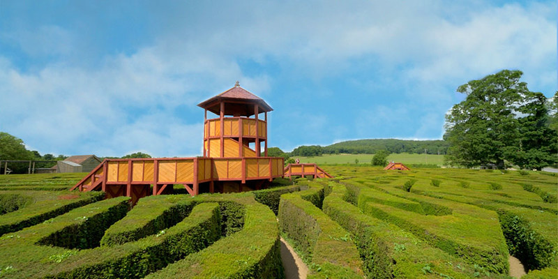 The grand Longleat green maze with redbrick house in the background set against a blue sky.
