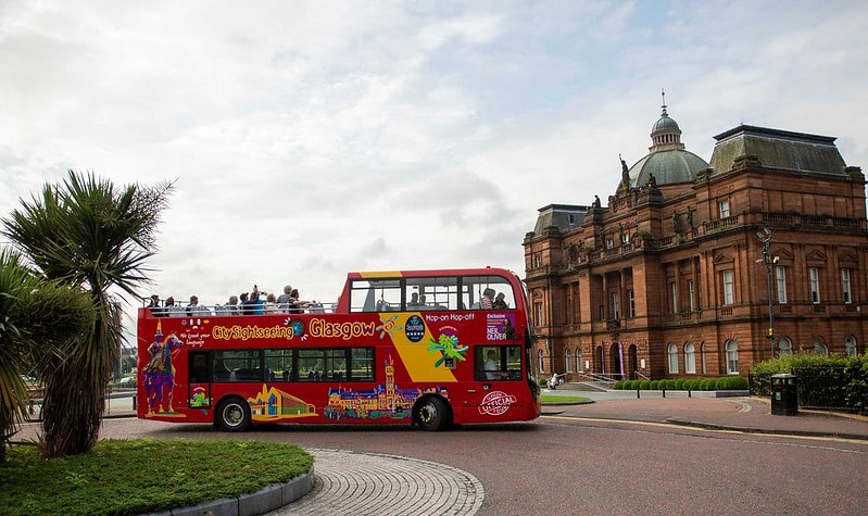 An open-deck hop-on, hop-off bus stopping outside of a grand building in Glasgow.