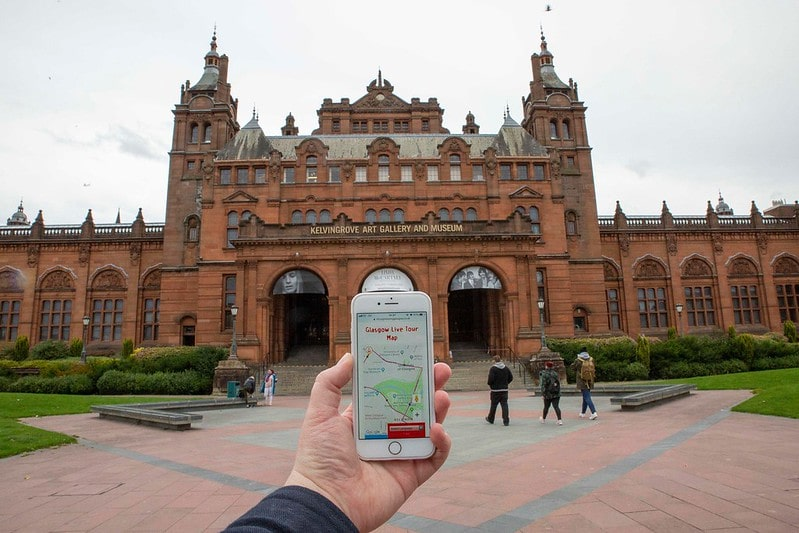 A hand holding a virtual bus tour map of Glasgow on their phone in front of a grand museum.
