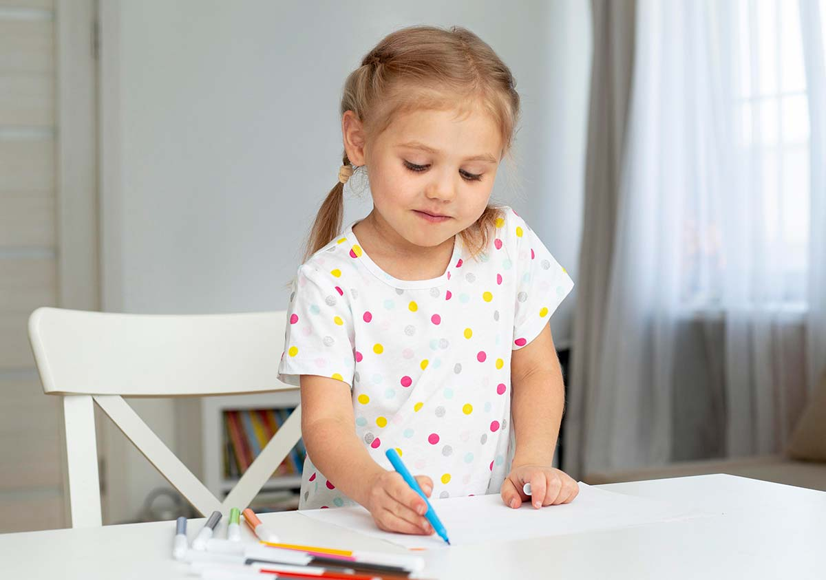 Little girl standing at the table colouring in a Gruffalo drawing.