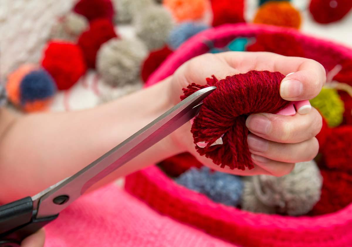 Close up of a hand cutting string with scissors to make a pom pom Gruffalo model.