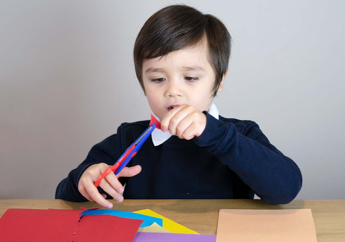 Little boy sat at a table cutting pieces of coloured paper to make a Gruffalo mask.