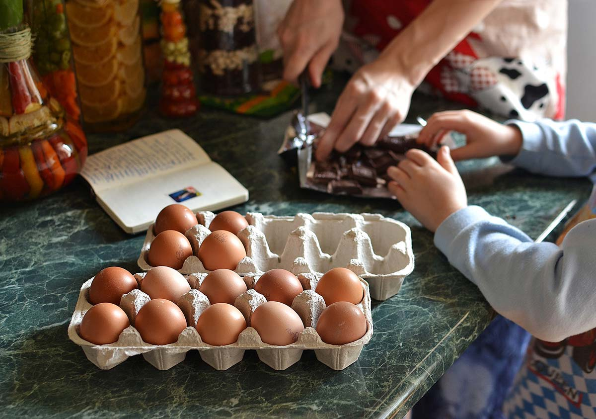 Close up of child cracking eggs into a bowl to make a football pitch cake.